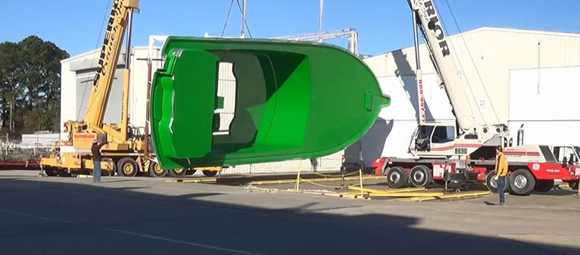A green molding of a Hatteras GT 70 is held sideways by a crane