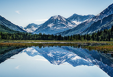 A scenic view of a mountain range in Alaska next to a lake, with grass and trees in between