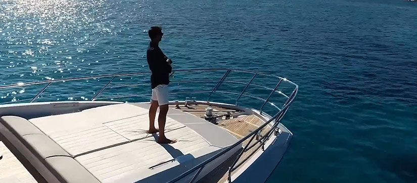 A man standing on the bow of a yacht