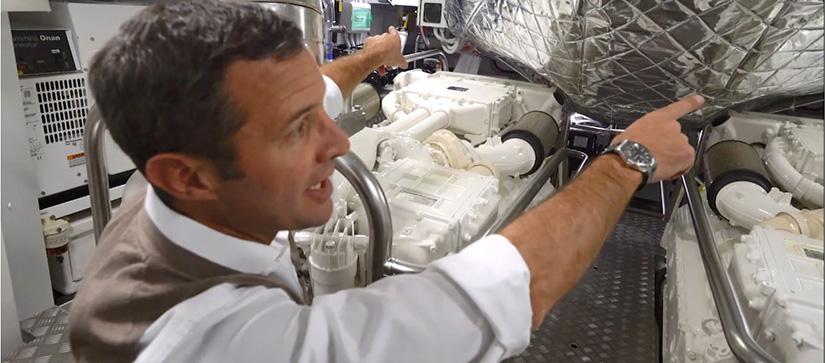 A man pointing at a machine in an Azimut Grande 25 Metri engine room