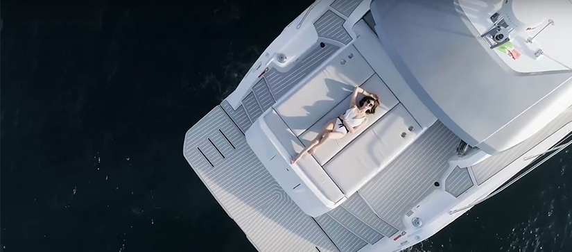 woman wearing white bathing suit laying on the aft deck on a large white yacht