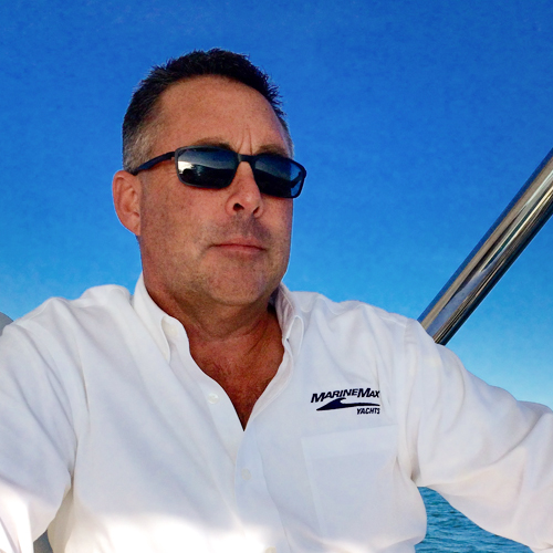 a man in sunglasses and a white polo looks off the stern of a boat
