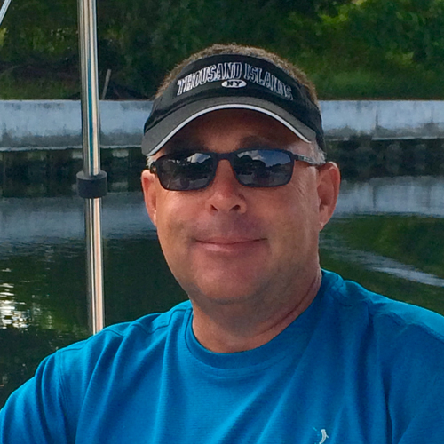 A man in a blue shirt and black visor smiles while standing on a boat