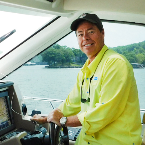 A man stands smiling at the helm of a boat
