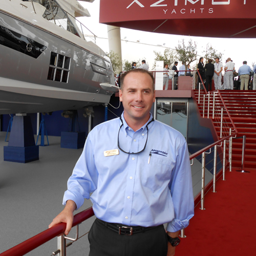 A man stands in front of a railing with an Azimut Yacht behind him