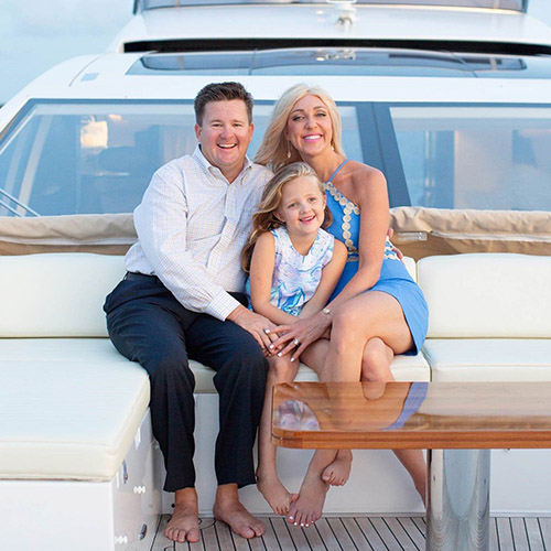 A man and woman sitting on a boat with their daughter sitting between them.