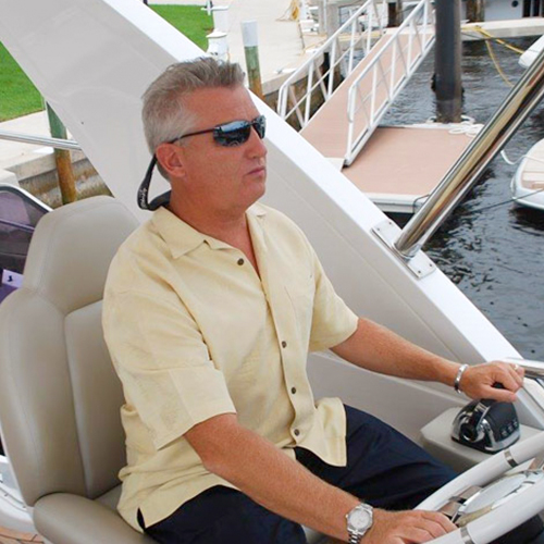 A man in sunglasses sits at the helm of a boat