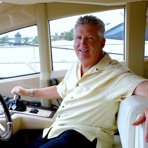 A man sits smiling at the helm of a boat