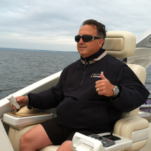 A man sits at the helm of a boat and gives thumbs up