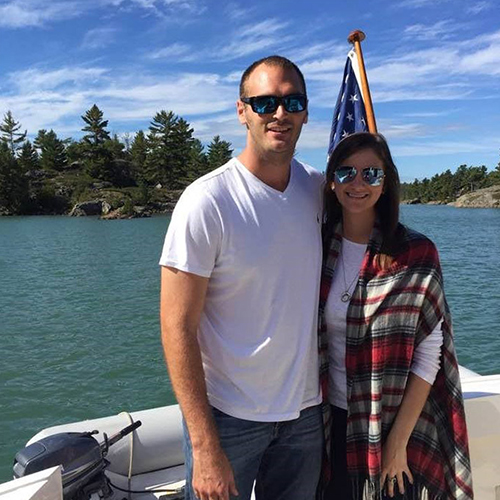 A couple stand on a boat with an American flag behind them