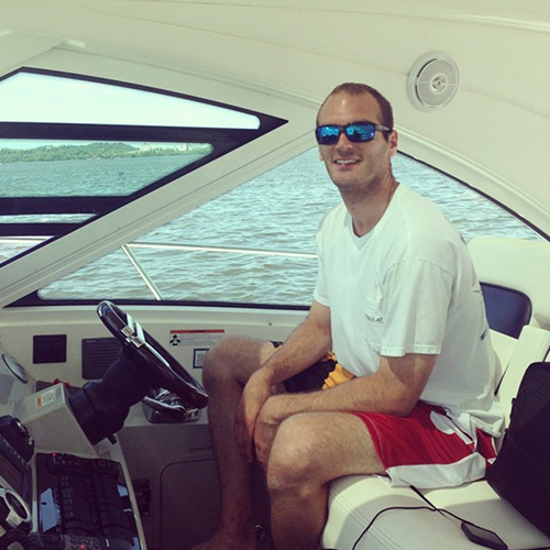 A man in sunglasses and a white shirt sits at the helm of a boat