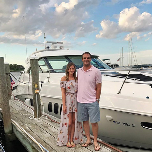 A couple stand on a dock with a boat behind them